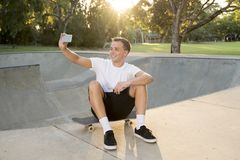 Man 30s sitting on skate board after sport boarding training session taking selfie photograph portrait or picture on mobile phone. Young happy and attractive Royalty Free Stock Images
