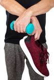 Man`s sporty footwear & dumbbell. Close up picture of man holding stylish sporty shoes and blue dumbbell on isolated background Royalty Free Stock Photo