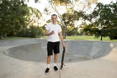 Man 30s standing holding skate board after sport boarding training session using mobile phone at half pipe track stock photography