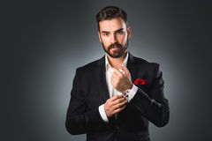 Man's style. Elegant young man getting ready. Dressing suit, shirt and cuffs Royalty Free Stock Images