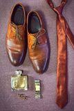 Man`s style. Men`s Accessories for groom. A set of clothes for the groom. Wedding shoes, belt, tie, perfume, cufflinks. The whole set of men is made in brown Stock Photography