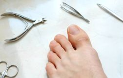 Man`s toenails with manicure tools. Foot and toes close-up. Top view. Man`s toenails with manicure tools. Foot and toes close-up. Top view Royalty Free Stock Photo