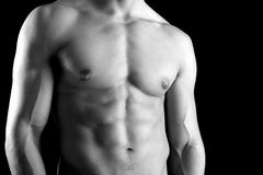 Man's torso. Ma's torso showing great abdominal muscles over a black background Royalty Free Stock Images