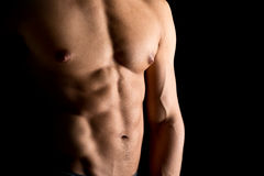 Man's torso. Ma's torso showing great abdominal muscles over a black background Royalty Free Stock Photography