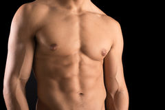 Man's torso. Ma's torso showing great abdominal muscles over a black background Stock Photos