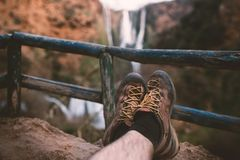 Man´s trekking shoes in a nature of Morocco - Ouzod falls. Close up of hiking boots against waterfall. Man hiking enjoying a view after trek royalty free stock photos