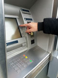 Man`s using the ATM machine with cash cards and entering PIN/pass code on keypad. Royalty Free Stock Image