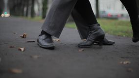 Man`s and woman`s feet in black leather shoes dance on ground covered by leaves. Man`s and woman`s feet in black leather shoes energetically dance in street on stock video footage