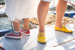 Man's and women's legs in color shoes. Bride and groom' legs in color shoes on yacht Stock Photo