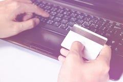 Man& x27; s wręcza używać laptop w domu podczas gdy trzymający kredytową kartę, linia robi zakupy w domu Zdjęcia Royalty Free