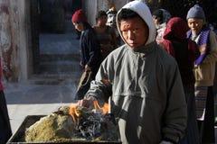 Man and sacrifice. KATHMANDU, NEPAL - CIRCA NOVEMBER 2013 Man burn sacrifine near Bodnath stupa Stock Image