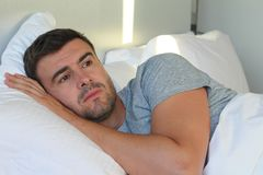 Man with sad expression in bed.  stock photography