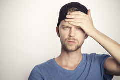 Man with sad face holding his hand against his forehead. Frustrated young man with cap on head Royalty Free Stock Photos
