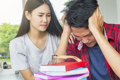 Man sad student checking a failed exam sitting together at table. University students doing group study Stock Image