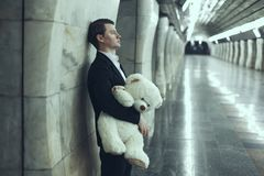 Man is sad with a teddy bear toy in his hands. The concept of his beloved woman did not come to the meeting stock images