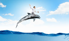 Man saddling dolphin Royalty Free Stock Image