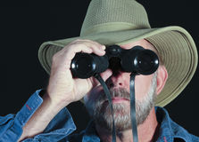 A Man in a Safari Hat Looks Through Binoculars Royalty Free Stock Photo