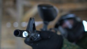 Man in safe glasses shooting with marker. Man in camouflage and safe helmet targeting and practicing in shooting with paintball marker stock footage