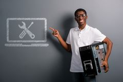Man in safety glasses holding computer. Black male in protective glasses holding a computer with one hand and pointing at Repair sign with the other. Big smile Royalty Free Stock Images