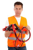 Man in safety vest. Holding car jumper cables over white background Stock Photos