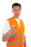Man in safety vest. Over white background is pointing at you stock photos