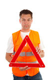 Man in safety vest. Holding foldaway reflective road hazard warning triangle over white background stock photos