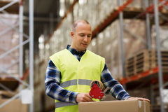 Man in safety vest packing box at warehouse Royalty Free Stock Photo