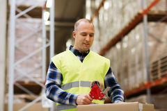 Man in safety vest packing box at warehouse Royalty Free Stock Image