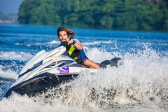 Man in Safety Vest Riding a Personal Watercraft during Daytime Stock Photo