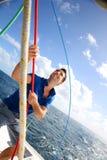 Man on sail boat. Young man lifting the sail of catamaran during cruising Stock Photo