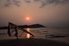Windsurfing sunset. Sunset sports men picking up windsurfing Royalty Free Stock Photo