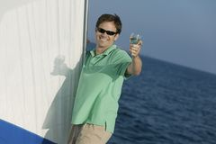 Man on sailboat, toasting with glass of wine Royalty Free Stock Photo