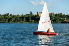 Man on sailing boat and windsurfer Stock Photo