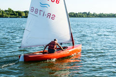 Man on sailing boat and windsurfer Stock Photography