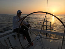 Man sailing sitting yacht deck sunset evening steering wheel Royalty Free Stock Image
