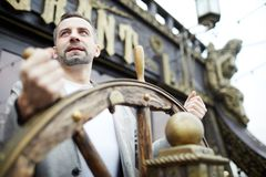Man by sailing wheel royalty free stock photo