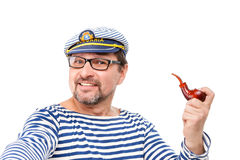 A man sailor in a cap with a smoking pipe in front of a white ba. Ckground Royalty Free Stock Photos