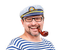 A man sailor in a cap with a smoking pipe in front of a white ba. Ckground Stock Image