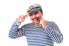 A man sailor in a cap with a smoking pipe in front of a white ba. Ckground Stock Photography