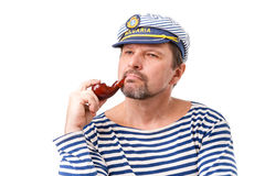 A man sailor in a cap with a smoking pipe in front of a white ba. Ckground Stock Photo