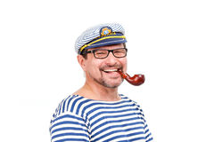 A man sailor in a cap with a smoking pipe in front of a white ba. Ckground Royalty Free Stock Photography