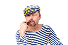A man sailor in a cap with a smoking pipe in front of a white ba. Ckground Royalty Free Stock Image