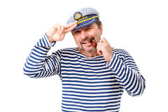 A man sailor in a cap with a smoking pipe in front of a white ba. Ckground Stock Photos