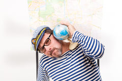 Man sailor in cap with smoking pipe, with globe and map, on whit Royalty Free Stock Photo