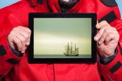 Man sailor showing cruise ship on tablet. Travel Stock Photography