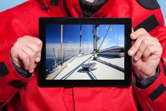 Man sailor showing yacht boat on tablet. Sailing Royalty Free Stock Photography