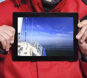 Man sailor showing yacht boat on tablet. Sailing Stock Photos