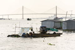 Man sails on ratty boat with fish farm raft houses floating on Mekong river with Rach Mieu Bridge in background Royalty Free Stock Photos
