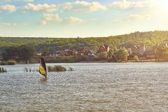 Man sails on a surfboard with a sail on the river. stock photo