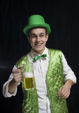 A man (Saint Patrick) smile in a green. Vest with a green hat and bow tie. He keeps a glass of beer in his hand. It is St. Patrick's Day Stock Photography
